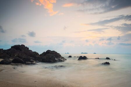 landscape mode: A dramatic scenic landscape shot of the beach and rocks  with beautiful sky and mountain in background, on a tropical island, shooting in long exposure mode, Samui island Thailand Stock Photo