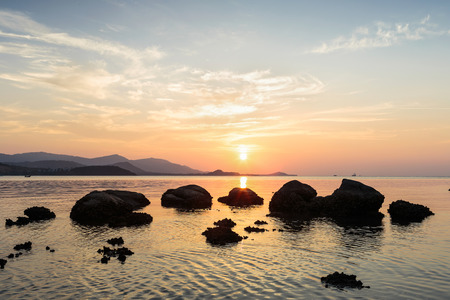 landscape mode: A dramatic scenic landscape shot of the rocks in the ocean with beautiful sky and mountain in background, on a tropical island, shooting in long exposure mode during summer time, Samui Island Thailand Stock Photo