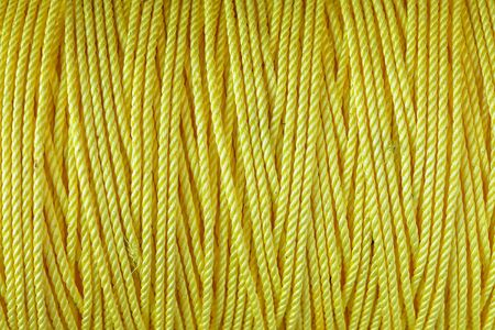 Strip of raw yellow nylon rope texture background
