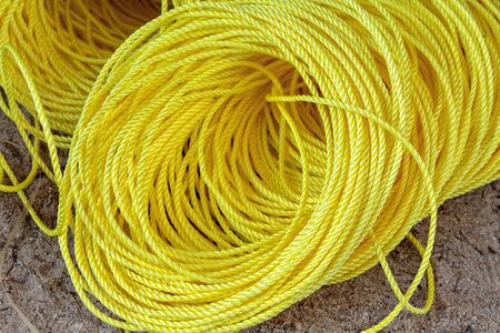 Coil of yellow synthetic rope on ground