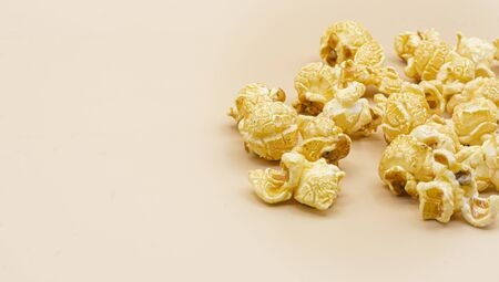 Delicious popcorn with caramel on color background