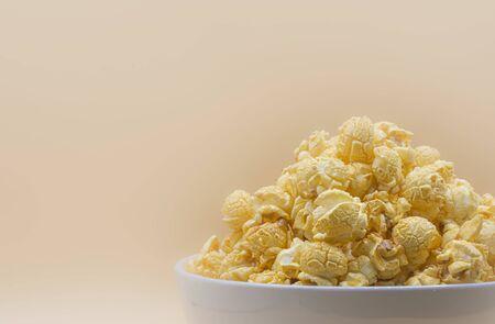 Delicious popcorn with caramel on color background Banco de Imagens