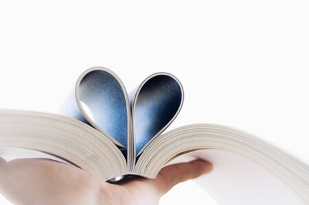Love of books, reading.  Open book with curled leaves in the shape of a heart. Stock fotó