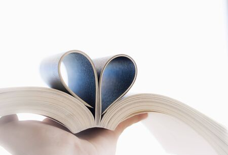 Love of books, reading. Open book with curled leaves in the shape of a heart.
