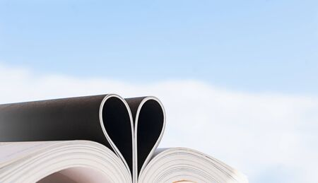 Love of books, reading.  Open book with curled leaves in the shape of a heart and blue sky. Stock fotó