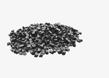Close-up of black plastic polymer granules on white background