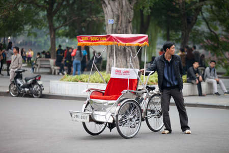 Traditional cyclo ride down the streets of Hanoi, Vietnam. The cyclo is a three-wheel bicycle taxi that appeared in Vietnam during the French colonial period.,September 19 2019 Editorial