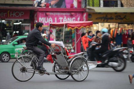 Traditional cyclo ride down the streets of Hanoi, Vietnam. The cyclo is a three-wheel bicycle taxi that appeared in Vietnam during the French colonial period.,September 19 2019
