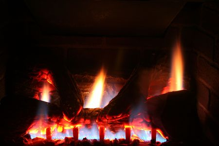gas fireplace: A natural gas fireplace burns in the dark. Stock Photo