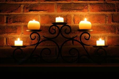 Candles on a wrought iron holder against a brick wall.