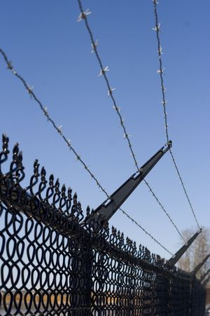 barbed wire fence: Barbed wire fence against a blue sky background. Stock Photo