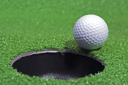 A golf ball sits beside the hole on the green. Reklamní fotografie