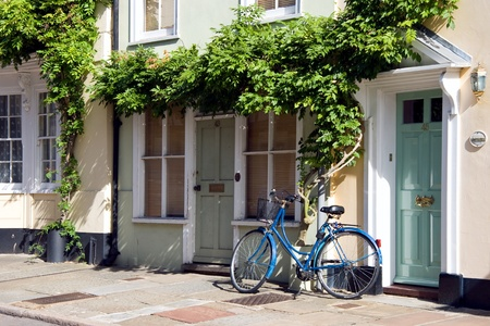 A blue bicycle leaning against a house in Sandwich Kent