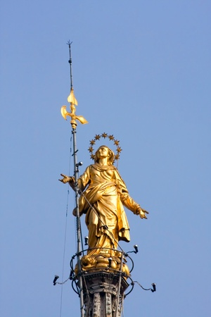Statue of Madunina on top of the Duomo Milan Italy photo
