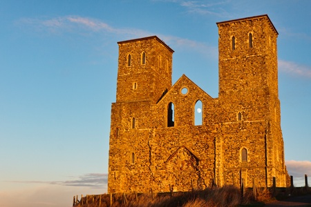 Remains of Reculver church towers bathed in late afternoon sun in winter photo