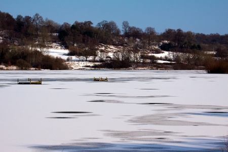 grinstead: Snow laying on the ice at Weir Wood Reservoir near East Grinstead Stock Photo