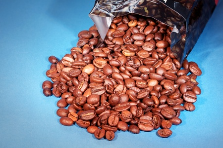 Close-up of coffee beans spilling out of packet photo