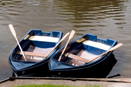 oars: Two rowing boats with oars moored on the River Coquet