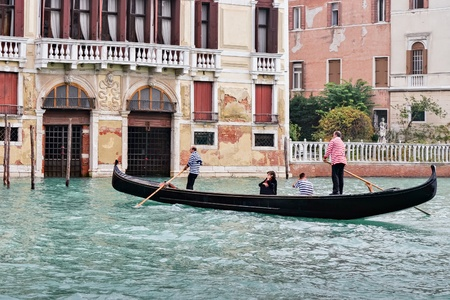 sightseers: Two gondoliers ferrying passengers along the canals of Venice