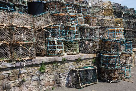 lobster pots: Lobster pots stacked against the harbour wall in Brixham Stock Photo