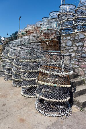 Lobster pots stacked against the harbour wall in Brixham photo