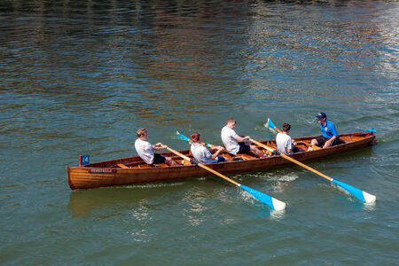 Onbekende man en jongens uitgeput aan het einde van een roeiboot race in Whitby Redactioneel