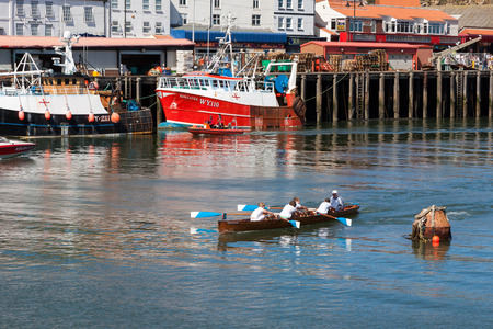 whitby: Unidentified man and boys exhausted at the end of a rowing boat race in Whitby