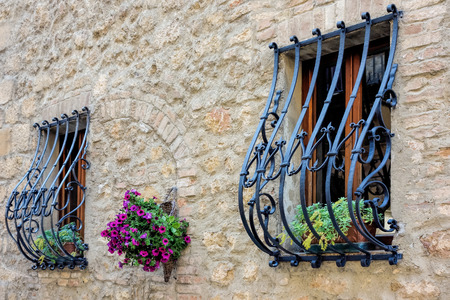 horizontal bar: Wrought iron security bars over windows in Pienza Stock Photo