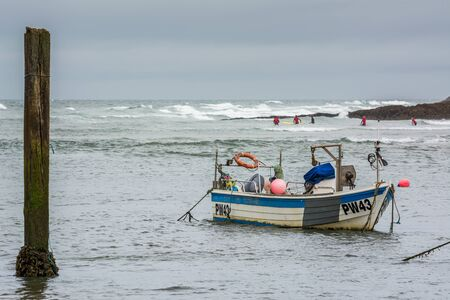 buoys: Boat and surfers at Bude
