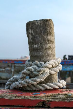 coiled rope: Rope coiled around a wooden post on a boat at Dungeness