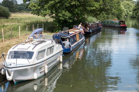 berkshire: Narrow boats on the Kennet and Avon Canal near Aldermaston Berkshire on July 5, 2015. Unidentified people.