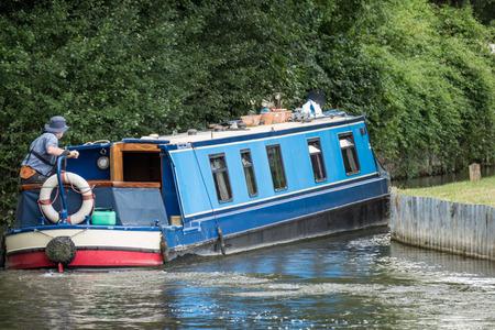 berkshire: Narrow boat on the Kennet and Avon Canal near Aldermaston Berkshire on July 5, 2015. Unidentified man Editorial