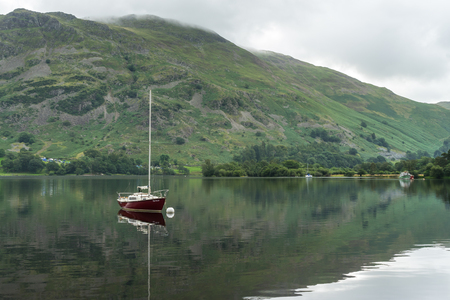 moored: Red Yacht Moored at Ullswater Stock Photo