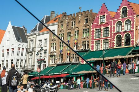 house gables: Split mirror of historic gabled buildings and cafes in Market Square Bruges West Flanders in Belgium
