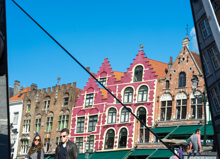 gabled: Split mirror of historic gabled buildings and cafes in Market Square Bruges West Flanders in Belgium