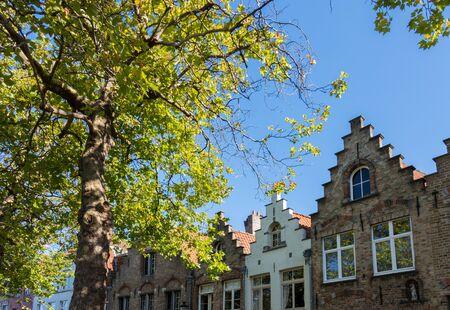 alongside: Buildings alongside a canal  in Bruges West Flanders in Belgium