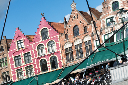 Split mirror of historic gabled buildings and cafes in Market Square Bruges West Flanders in Belgium