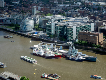 hms: HMS Belfast and other Boats Moored in the Thames Editorial