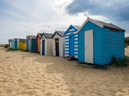 brightly: A Row of Brightly Coloured Beach Huts in Southwold Stock Photo