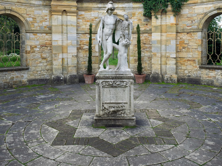 unclothed: Old Statue of a Young Man and Eagle in the Garden at Hever Castle Editorial