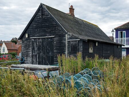 Lobster Pots in the Undergrowth outside a Storage Shed in Aldeburgh Stock Photo