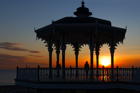 BRIGHTON, EAST SUSSEXUK - JANUARY 26 : View of the sunset from a bandstand in Brighton East Sussex on January 26, 2018. Unidentified people.