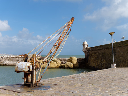 Old Crane outside Fort Ponta da Bandeira in Lagos, Algarve Portugal Stock Photo