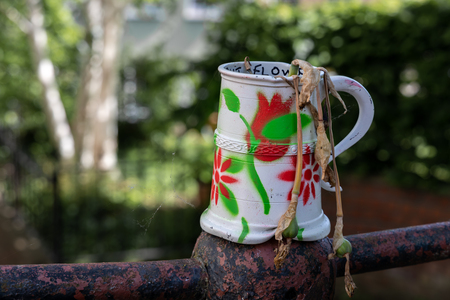 Old dented and painted tankard containing dead daffodils