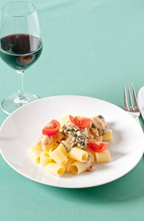 Chicken with pasta and fresh cherry tomatoes on a pastel tablecloth photo