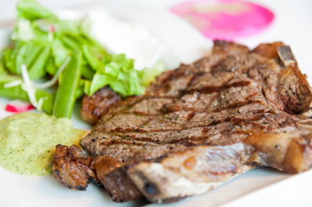 sallad: Steak with marks on a white plate with some sallad