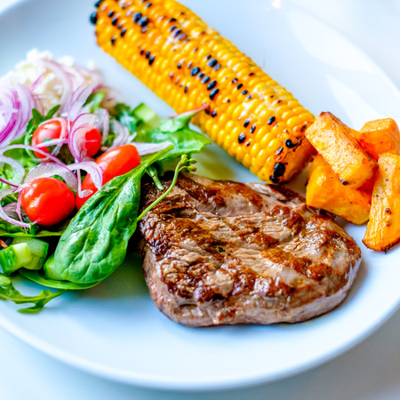 sallad: Grilled Beef Steak with some sallad on the side and corn