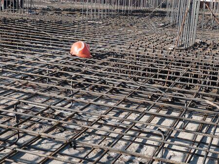 Orange hardhat on the steel grid of residential building footing reinforcement. 스톡 콘텐츠