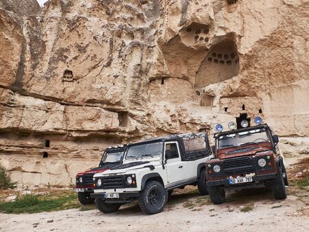 Goreme, Turkey - October 2019. Three Land Rover offroad cars park in front of typical cappadocian cave house remains