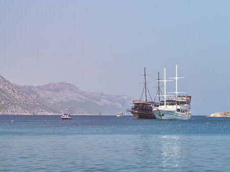 Yacht da crociera nautici nella baia del Mar Mediterraneo. Navi da crociera ricreative marine nel pomeriggio soleggiato. Tisan, provincia di Mersin, Turchia Archivio Fotografico